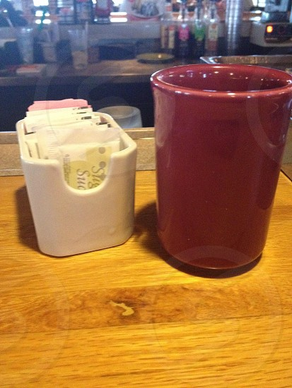 white ceramic dispenser beside red ceramic canister on brown wooden table photo