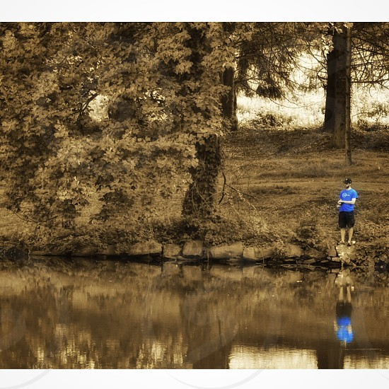 selective-color photography of man wearing blue crew neck t-shirt standing near body of water with reflection on the water photo