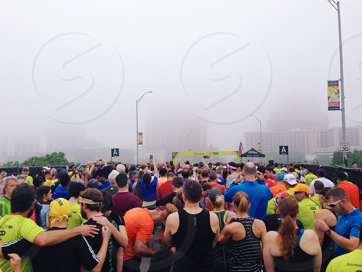 people standing on road behind starting line during misty morning photo