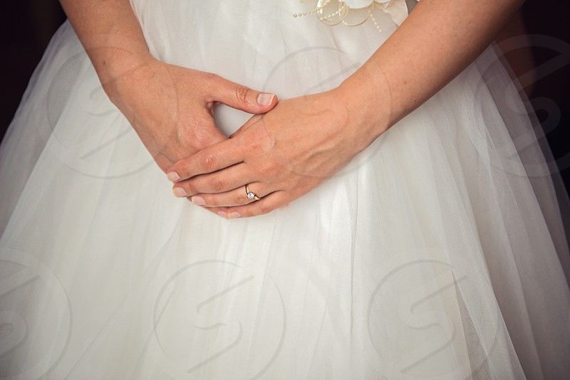 Bride hands on wedding dress with a ring photo