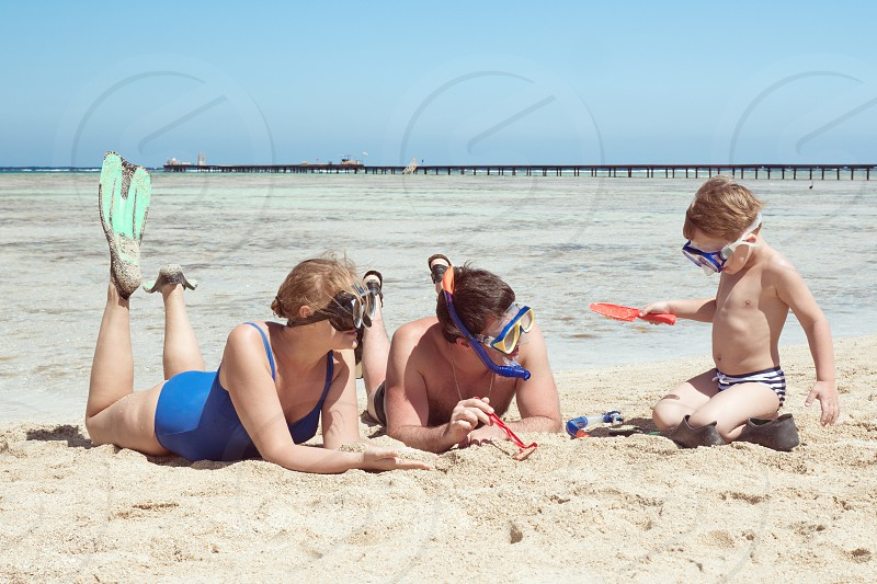 Mother father and little son on summer vacation at the seaside They wearing snorkels and flippers while lying and playing on the beach photo