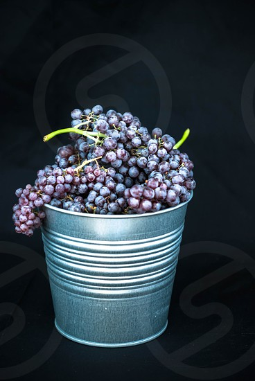Grapes in Metal Bowl on Black Background photo