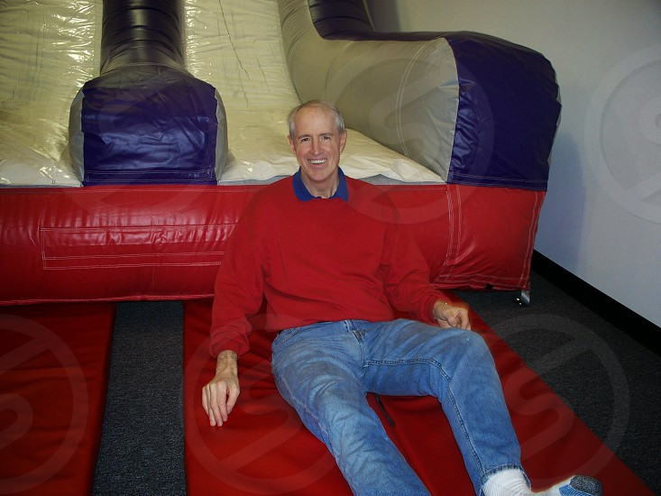 man indoor inflatable happy slide smiling photo