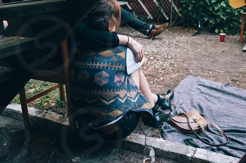 woman seated in aztec vest near crossbody saddle bag photo