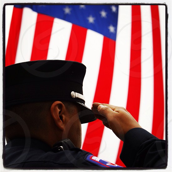 Fire fighter salutes during a memorial service. Salute. Firefighter. American Flag. photo