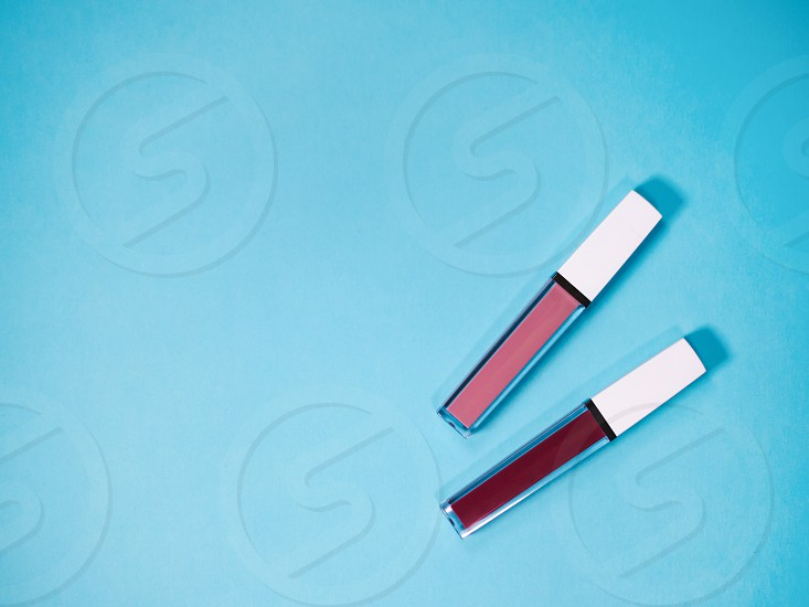 beautiful beige and red lip glosses isolated on blue background. photo