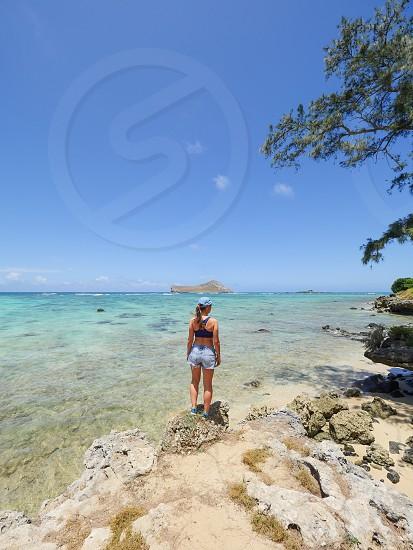 Woman standing on rock at Hawaiian tropical beach nature environment lifestyle outdoor Hawaii  photo