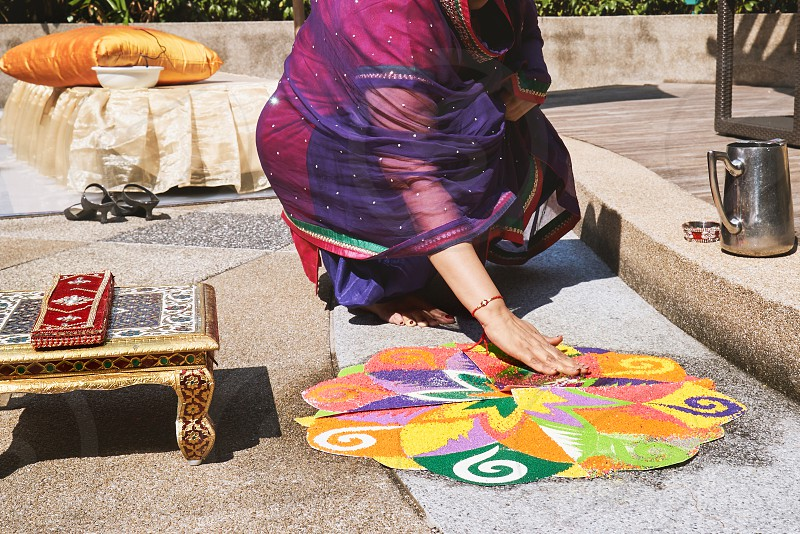 Women decorating and coloring tradition colorful rice art or sand art (Rangoli) on the floor with paper pattern using dry rice and dry flour with colored from natural pigments like sindoor haldi (turmeric) photo