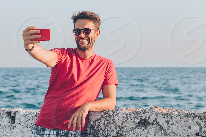 Young man tourist taking selfie with smartphone by the sea photo