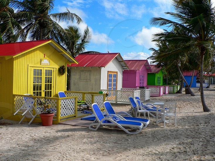 Princess Cays Bahamas beach bungalows sand lounge chairs palm trees colorful vacation paradise  photo