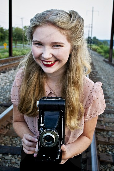 girl in pink ruffled blouse on train track smiling holding old fashioned black camera photo