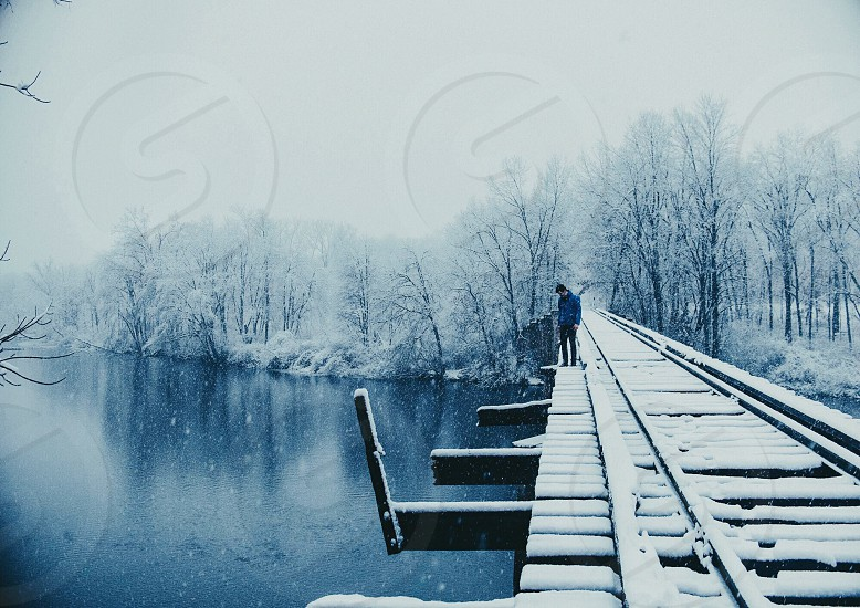 man standing on wooden bridge above the river photo