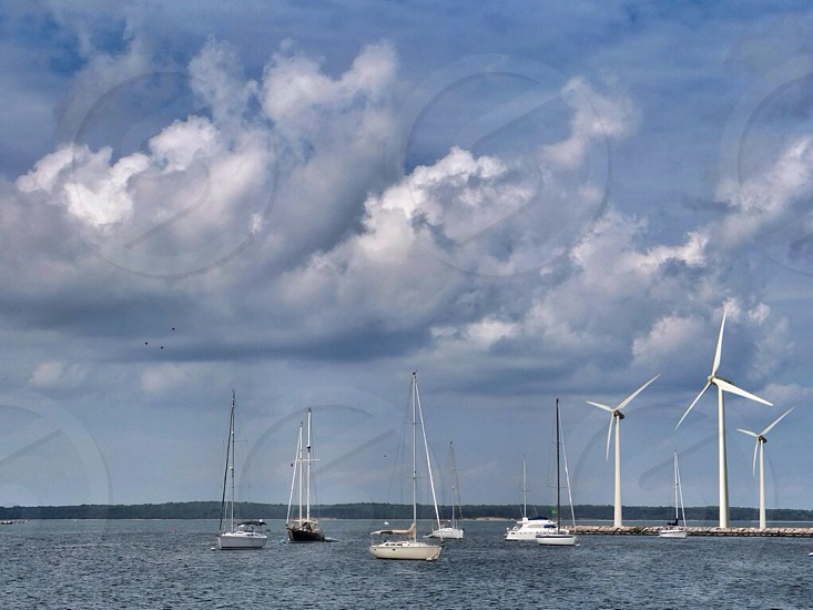 wind turbines near boats on body of water under cloudy sky at daytime photo
