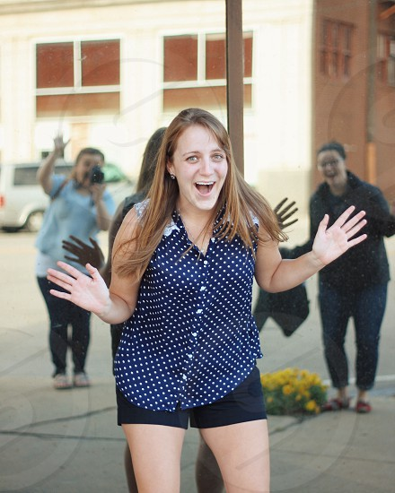 woman in white and blue polka dotted button up sleeveless blouse doing surprise gesture during daytime photo