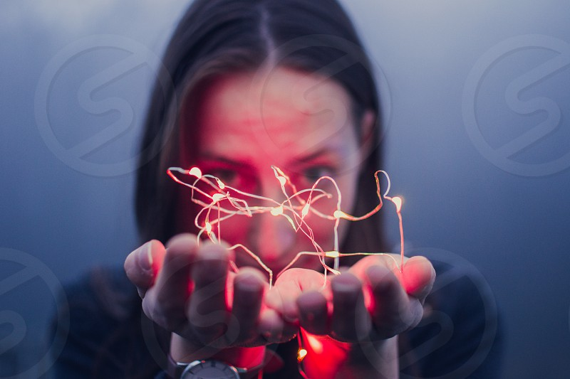 Close up of a girl's face holding red fairy lights. photo