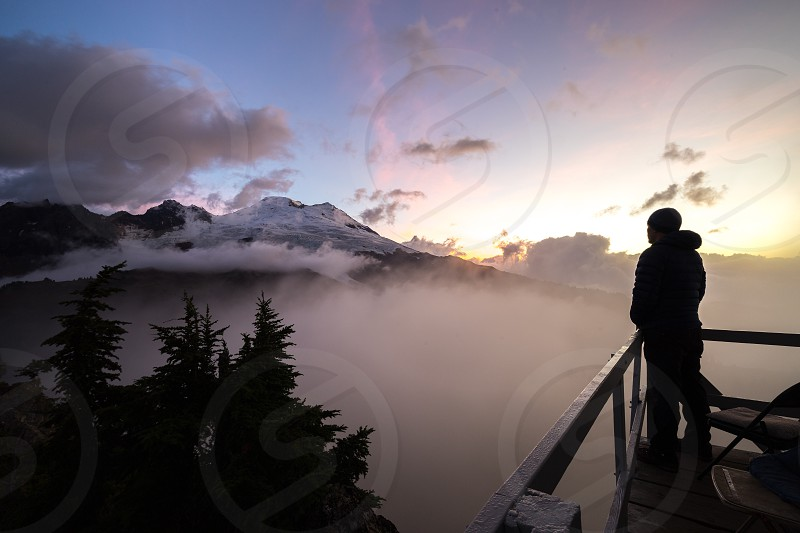 person in black hoodie standing on veranda near trees with mountain alps at distance over white clouds photo