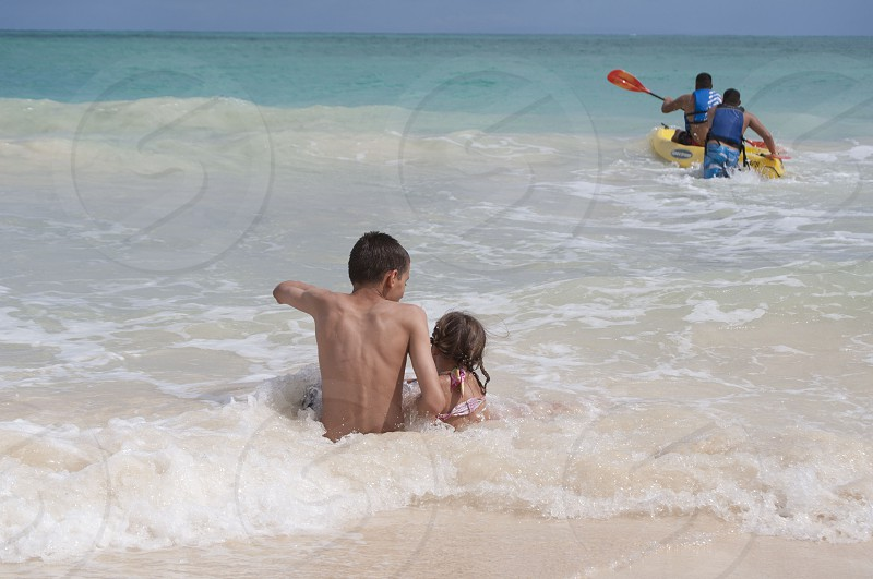Boy and Girl in Ocean Water on Beach photo