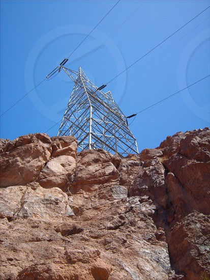 transmission tower and power lines below blue sky during daytime photo