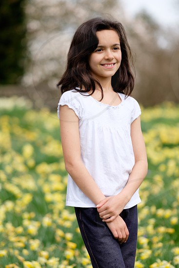 Portrait of a young dark haired girl with a gentle smile on her face looking away from the camera in a white top and dark blue leggings standing in a garden with yellow daffodil flowers behind her out of focus photo
