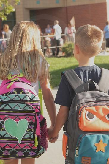 School boy girl summer school kids child grade backpack hands holding walking outside photo