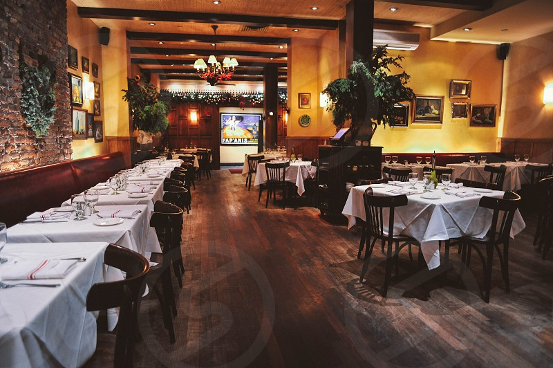 interior restaurant view with white table linens and wood chairs on wood floors photo