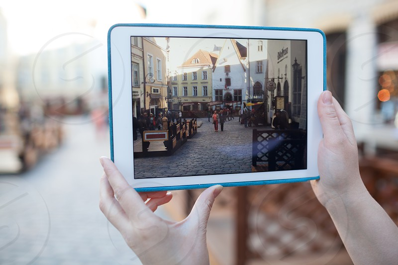 TALLINN ESTONIA - APRIL 22 2014: Close-up shot of womans hands using touchpad to make video or photo of ancient street in Tallin old city photo