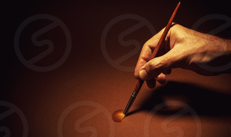 Conceptual composition paintbrush in a hand on brown background. photo