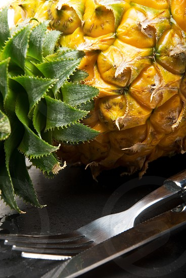 ripe pineapple on a black plate with knife and fork photo