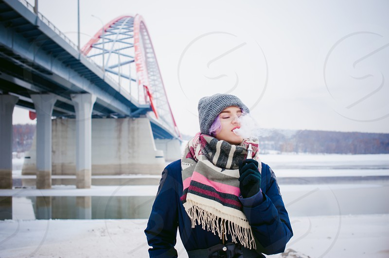 vaping girl. winter street portrait of a woman hipster purple-dyed hair a gray knitted hat and scarf. woman smokes an electronic cigarette in the street near the snow-covered river photo