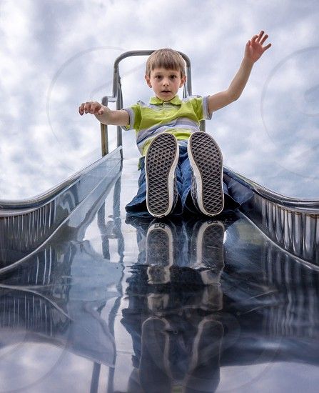 child in a green shirt on a slide photo