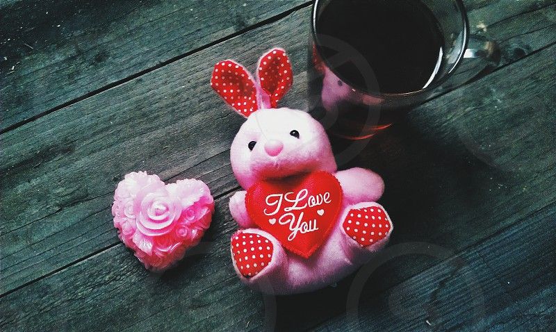 pink and red rabbit plush toy near clear drinking glass with coke soda photo