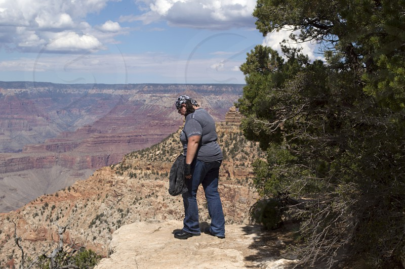 Woman peer over the edge of a drop off into the depths of the Grand Canyon. photo