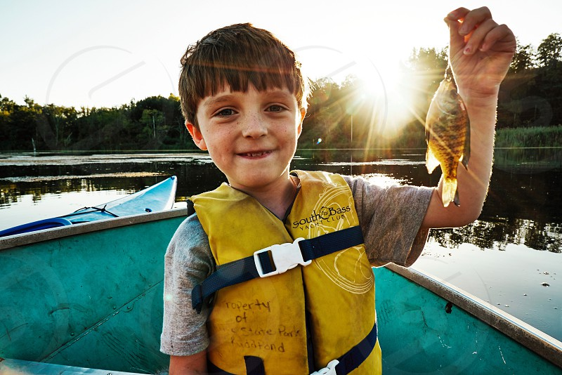 Kids child youth summer fishing fish nature excitement bluegill first catch sun flare warmth positive happy pond lake boat adventure  photo