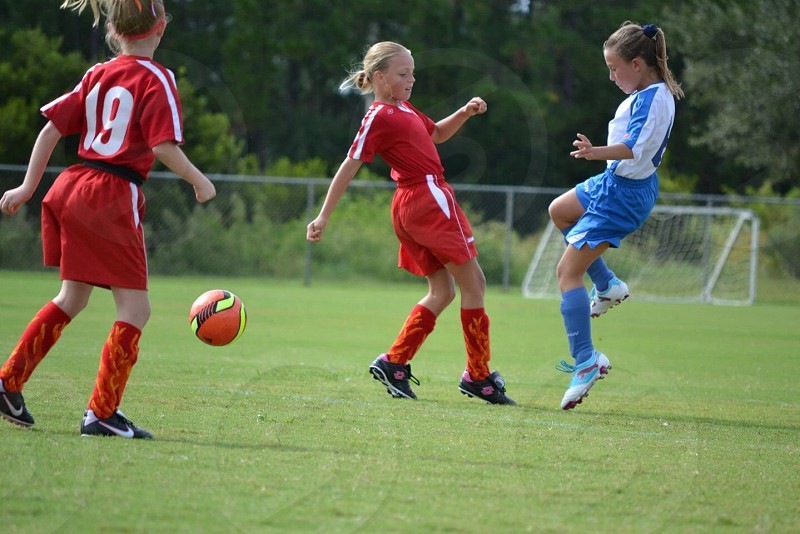 girl's soccer game red white  versus white blue photo