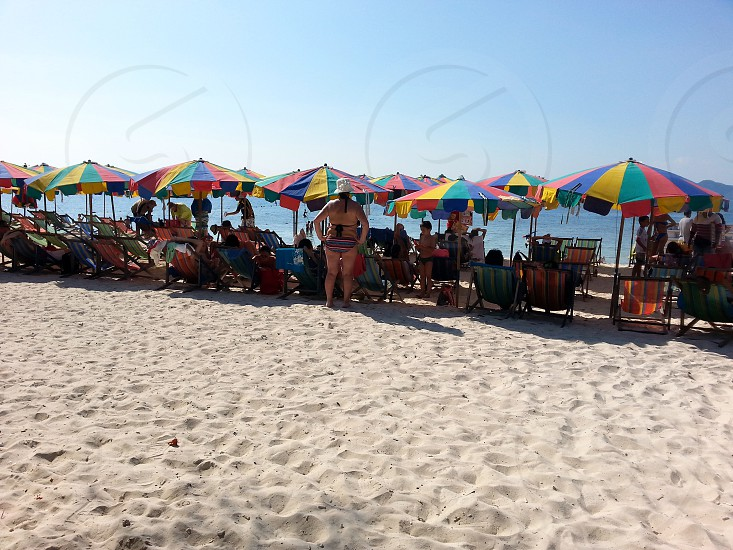 people with umbrellas near the sea during daytime photo