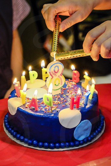 Close-up of hands lighting birthday cake for eighth years old kid photo