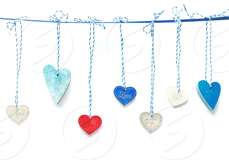 Colored wooden hearts on white background photo