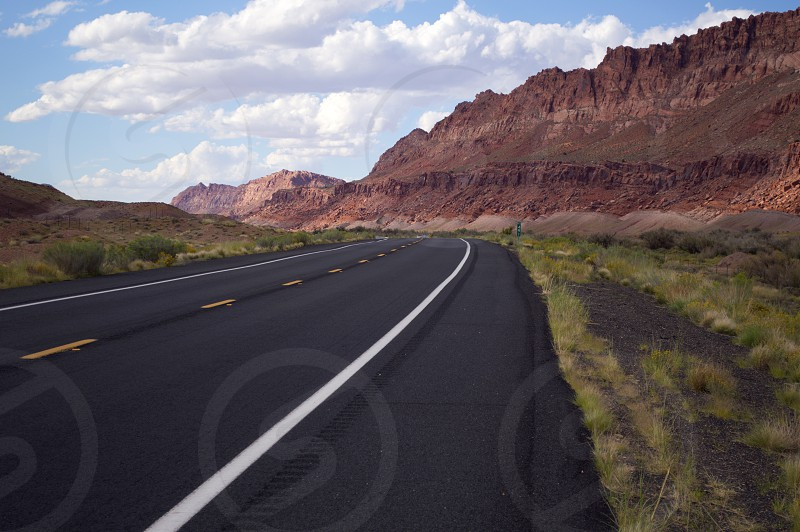 Empty highway leading off into the beautiful red hills of Northern Arizona around the Grand Canyon. photo
