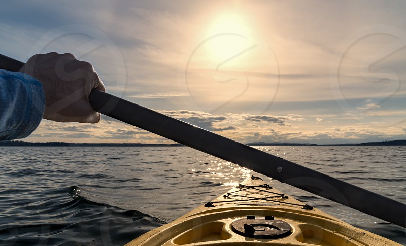 Point of view paddling a kayak out to sea at sunset. photo