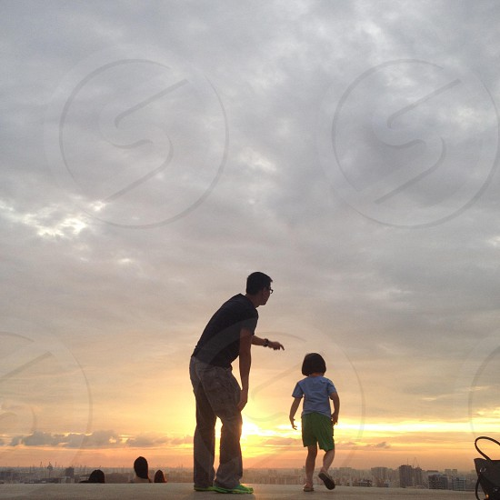 man in black shirt standing beside girl in purple shirt under cloudy sky with sunset view photo