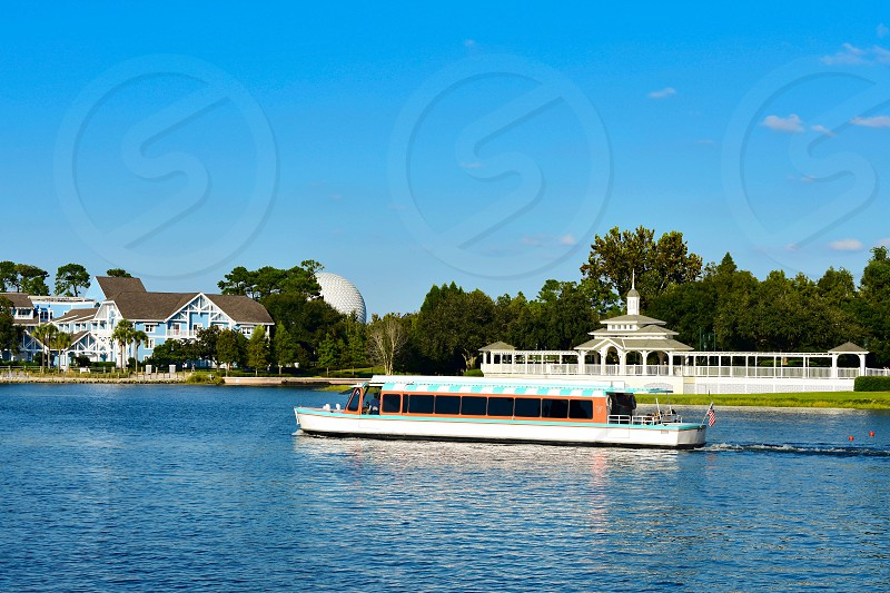 Orlando Florida. February 09 2019 . Taxiboat sailing on lake and partial view of Epcot sphere at Lake Buena Vista area. photo