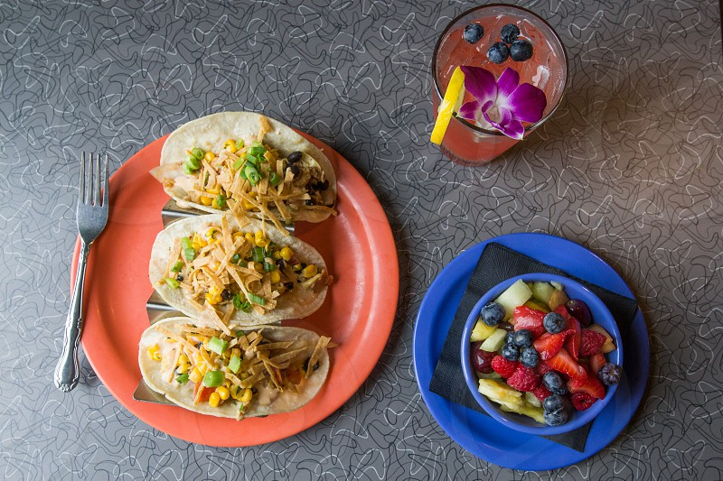 3 tacos in orange round plate besides slice strawberry mulberry and pineapple in blue round plate beside clear glass cup with juice photo