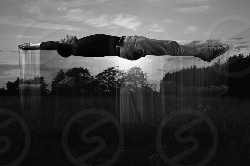 man levitating in a field on a sunset monochrome photography photo