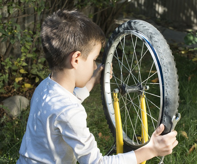 Child who fix bikes. Boy and bicycle photo