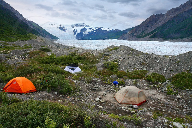 Tents along the Root Glacier in Wrangell-St.Elias National Park Alaska.  Stairway Icefall a massive 7000 foot cascade of ice is in the distance. photo
