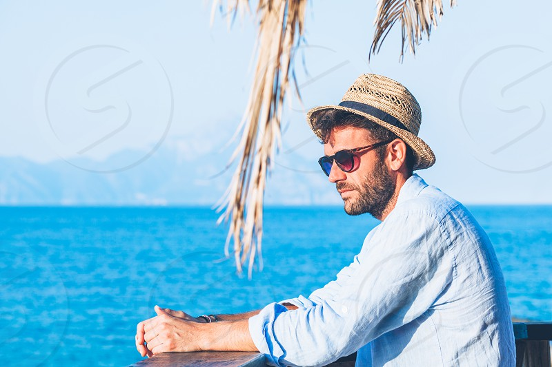 Young handsome man enjoying the view at the beach bar photo