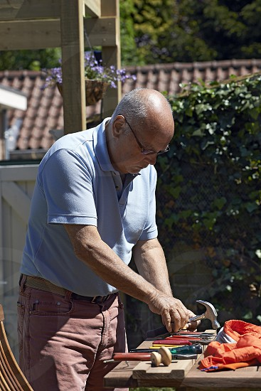 Elderly man outdoors in the back garden fixing something using some tools photo