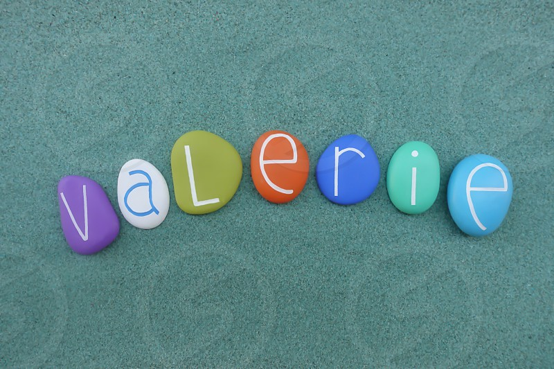 Valerie feminine given name composed with multi colored sea stones over green sand                            photo