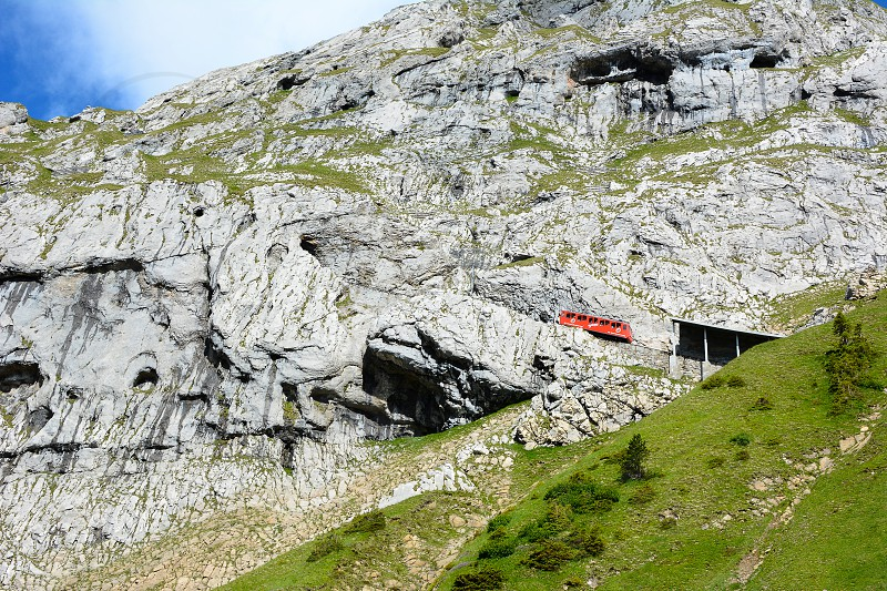 ALPNACHSTAD SWITZERLAND - July 3 2014: The Pilatus-Bahn the world's steepest cogwheel railway with a car about to enter a tunnel on Mount Pilatus. photo