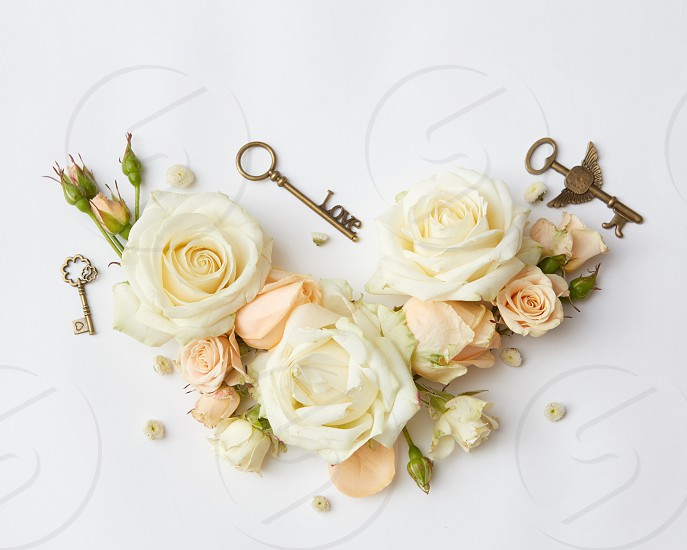 Vintage keys with beige roses on the background Flat lay. photo